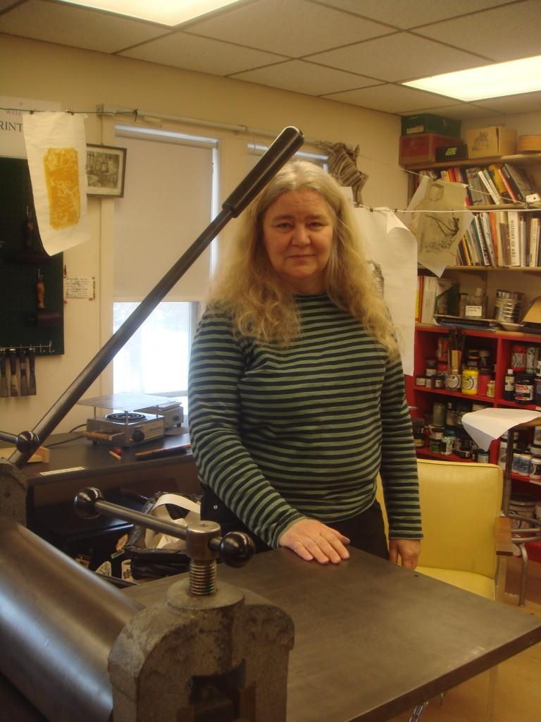 Professor Ruthann Godollei poses with the printing press in the Studio Art's makeshift Printland, located on the third floor of the Lampert Building. (Photo by Amy Lebowitz.)