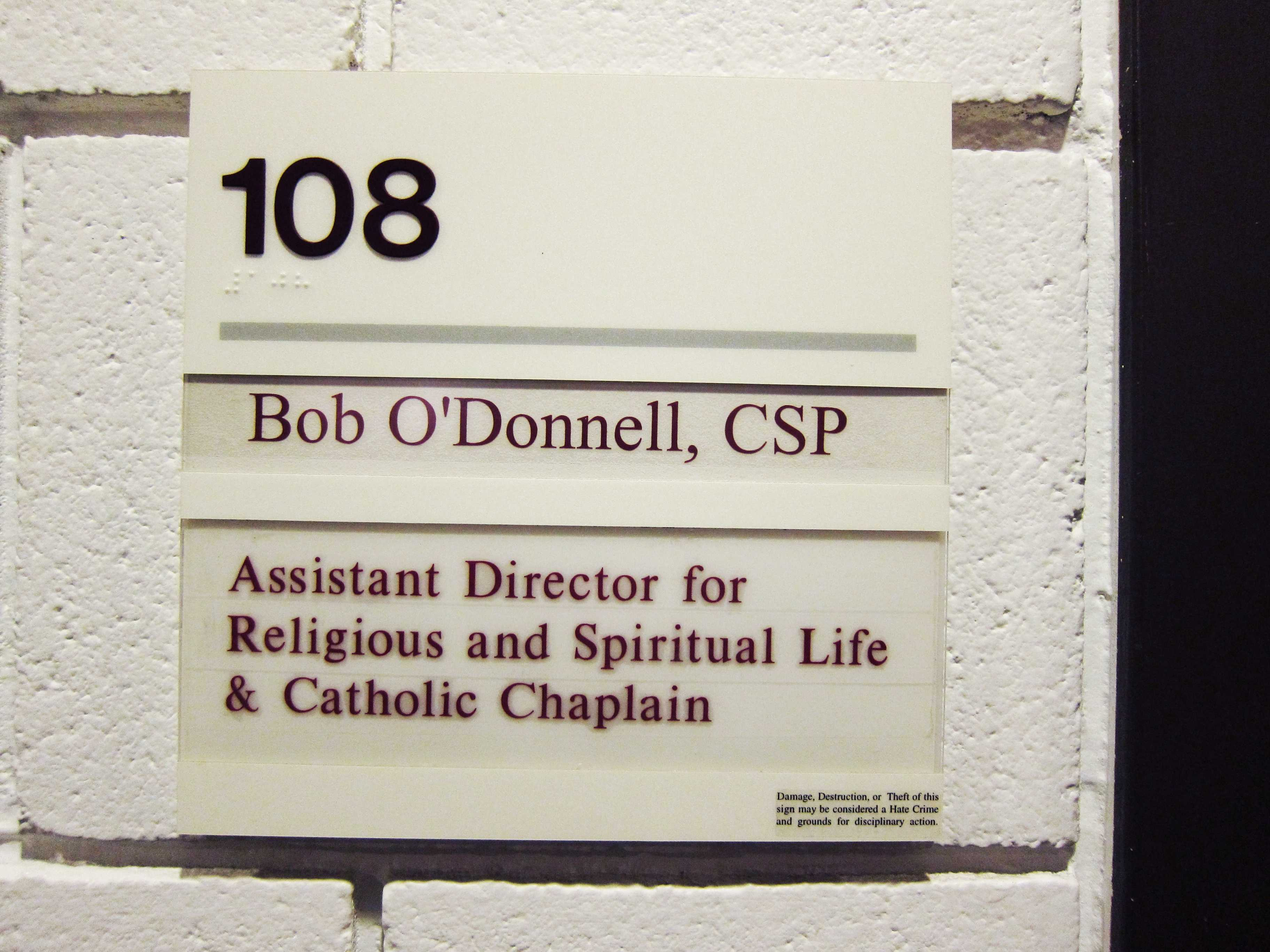 The sign outside the door to Catholic Chaplain Bob O'Donnell's former office remains up, even after O'Donnell's departure from Macalester. The CRSL is searching for a replacement priest after O'Donnell received word he would be reassigned elsewhere. Photo by Naomi Guttman '16.