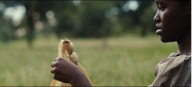 """Patsey makes a doll out of corn husks after a day of working Epps' cotton fields. Patsey, played by Lupita Nyong'o, is the only other slave the audience really gets attached to, yet is unable to escape slavery. Screenshot from the trailer for """"12 Years A Slave,"""" Fox Searchlight Pictures."""