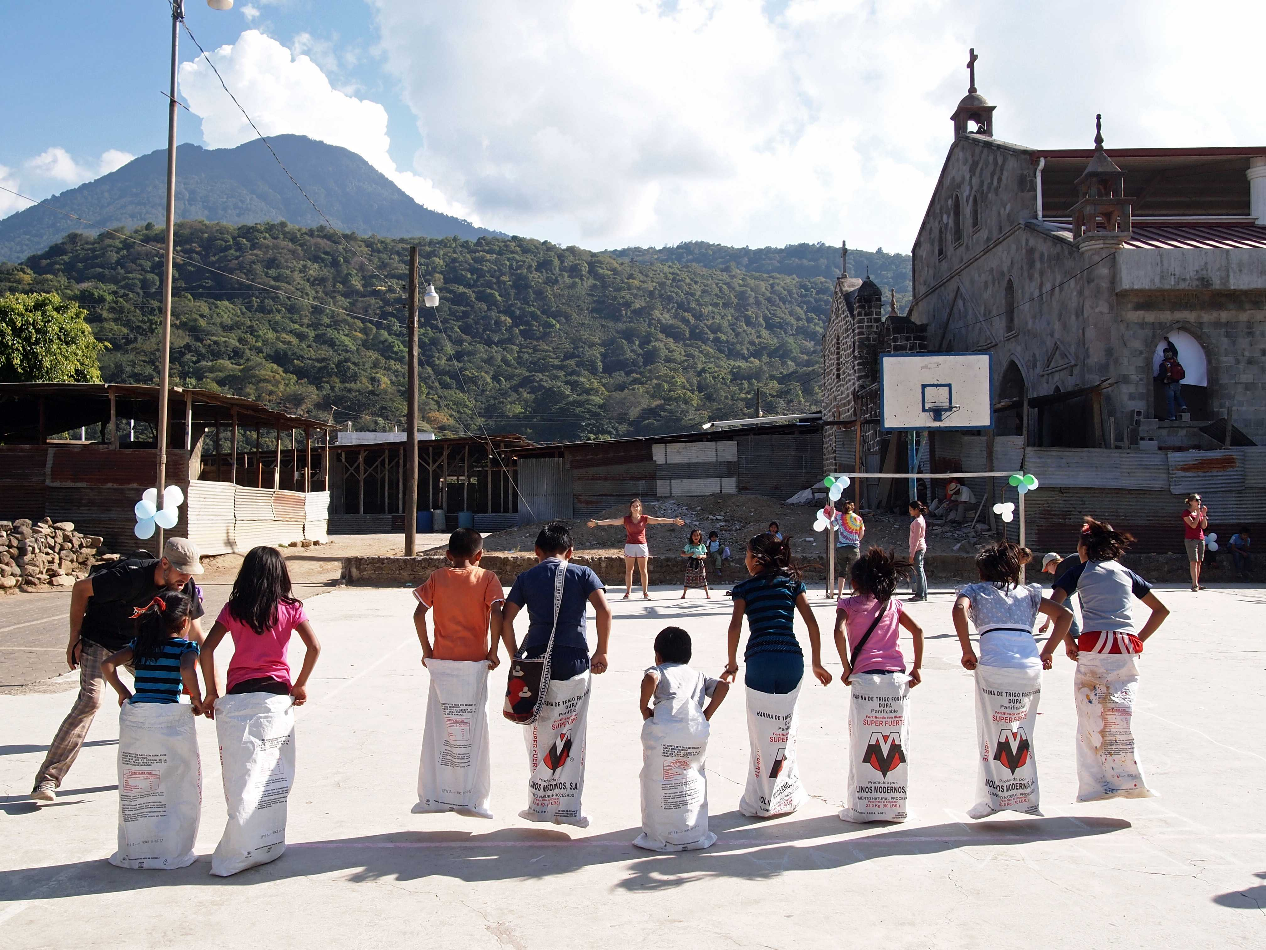 Guatemalan children compete in sack races during a carnival led by Rising Minds participants.