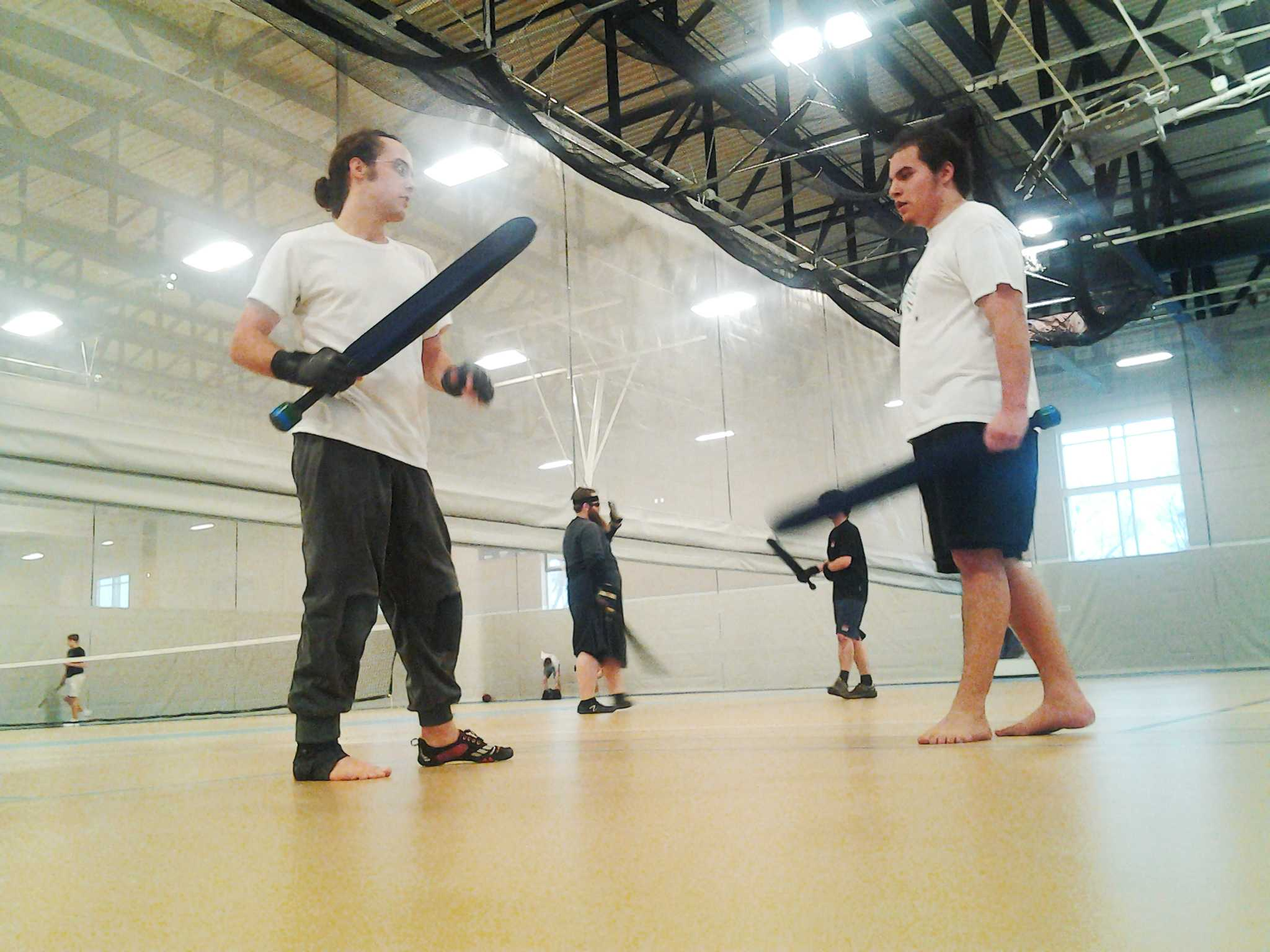 AJ Zozulin '14 (left), who helped found Mac's Dagorhir club after starting a similar group at his high school, holds a fighting stance in a Saturday afternoon practice. Waabanang Hermes  '17 (right), is about to embark in a practice duel.