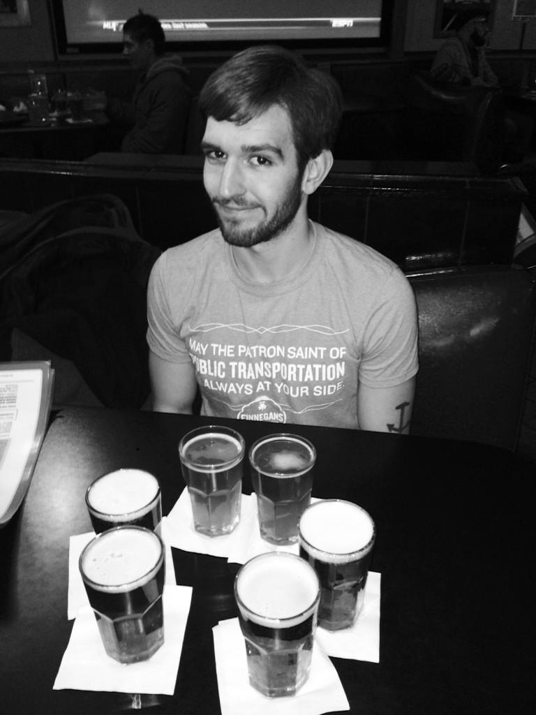 Mike Jones '14, anchor tattoo and all, pictured with a sampling of beers at Liquor Lyle's.  Photo courtesy of Lucy and Taryn