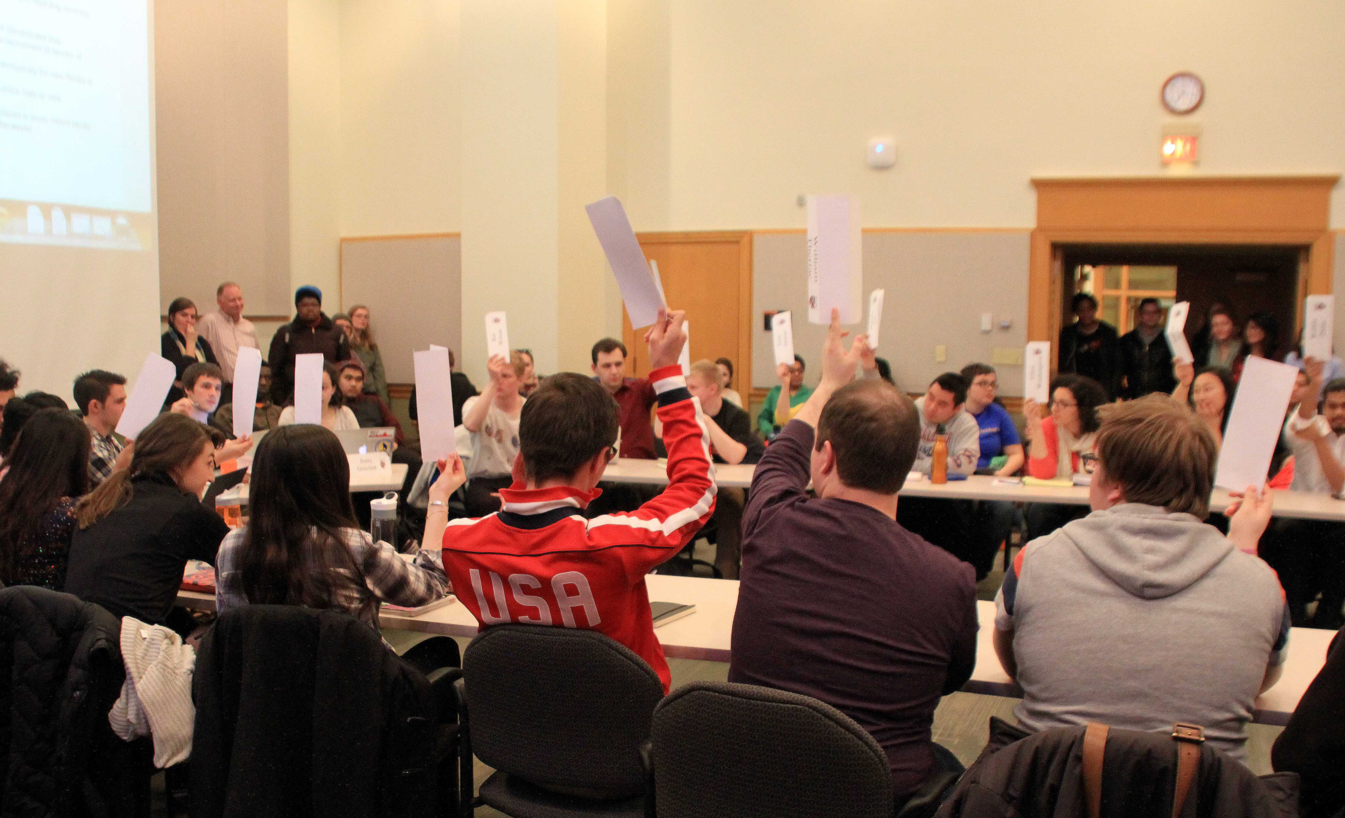 25 placards went into the air Tuesday night as MCSG unanimously passed a resolution calling on the school to commit to hiring more faculty members of color. Over 100 supporters packed the Weyerhaeuser Boardroom Tuesday night to express support for the bill. Photo courtesy of Emma Pulido '16.