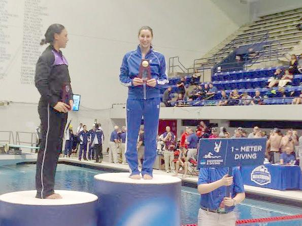 Renee Jordan stands on the podium after finishing first in the one-meter diving event at the NCAA Division III Swimming and Diving National Championships. Jordan's achievement ranks as our top Mac sports moment of the 2013-14 academic year. Photo courtesy of Rene Jordan '14.