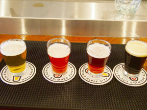"""Beer sampling (from left to right): India Pale Ale (6.4 percent ABV with flavors of citrus, pine and a dank aroma), Razz Roselle (5.7 percent ABV — a hibiscus sour Saison that tastes like summer raspberries), Hibiscus Roselle (5.7 percent ABV — a flowery LÄCTOBÄC Sour beer) and the Stout (5.5 percent ABV— an American stout featuring oats and a lightly-roasted malt for smooth, complex flavor). The raspberry Roselle won """"Best Beer"""" at Minnesota Brewer's Guild's Winterfest 2016 and was my personal favorite. Photo by Jesse Meisenhelter '16."""