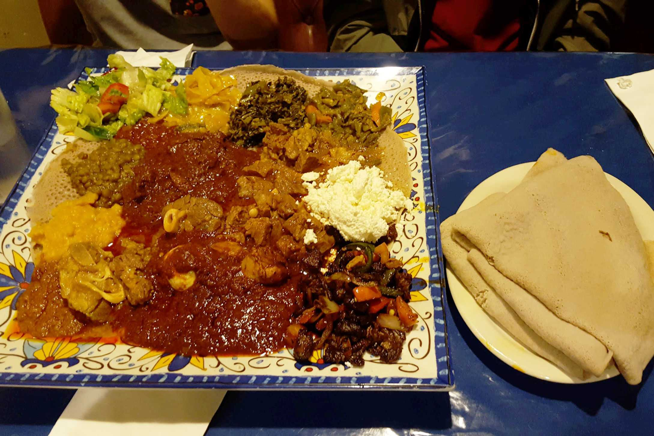 "Fasika offers the ""Ultimate"" plate, a mix of meats and vegetables served on injera. Photo by Henry Nieberg '19."