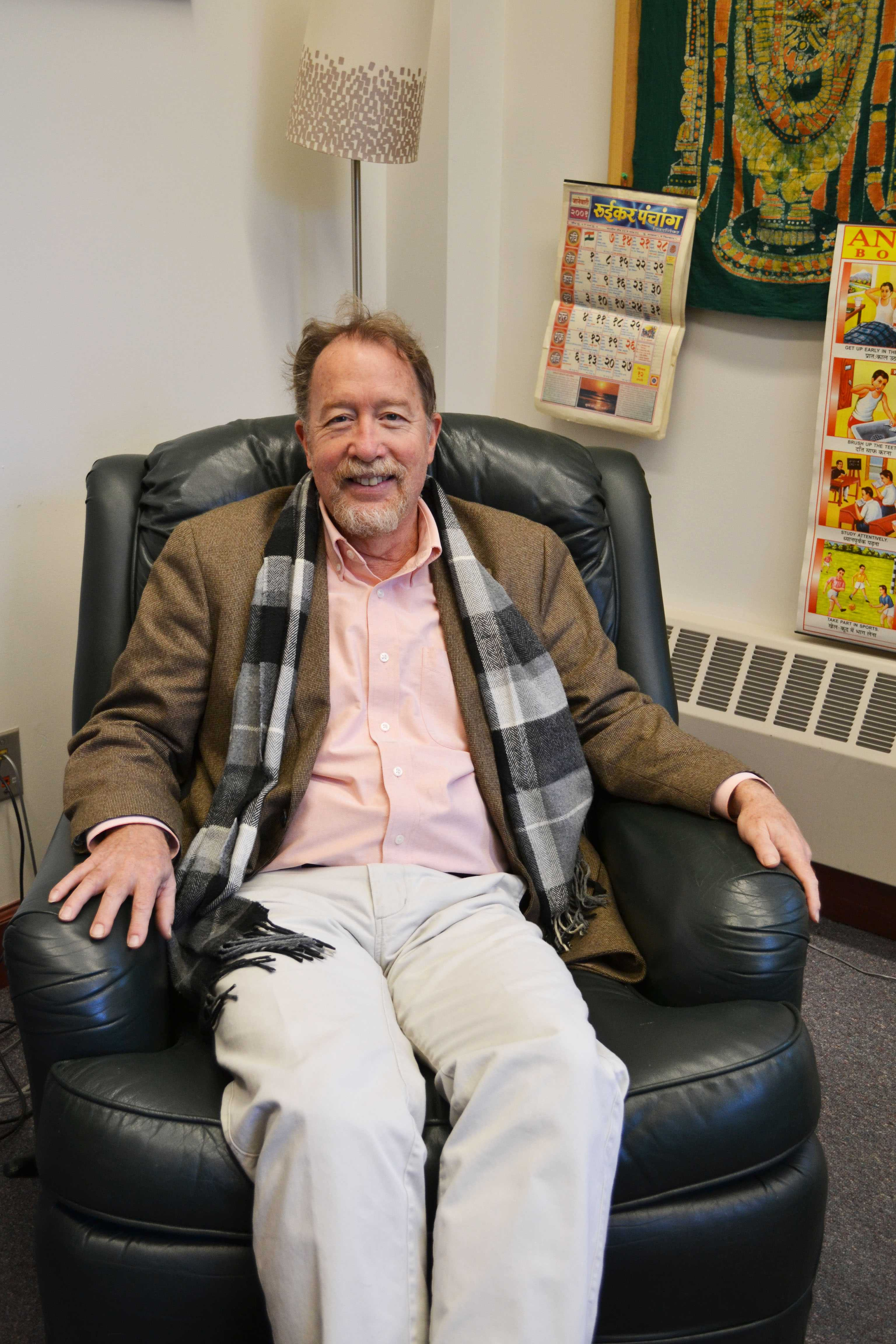 Professor Jim Laine poses alongside his office decorations. Photo by Alta Connors '19.