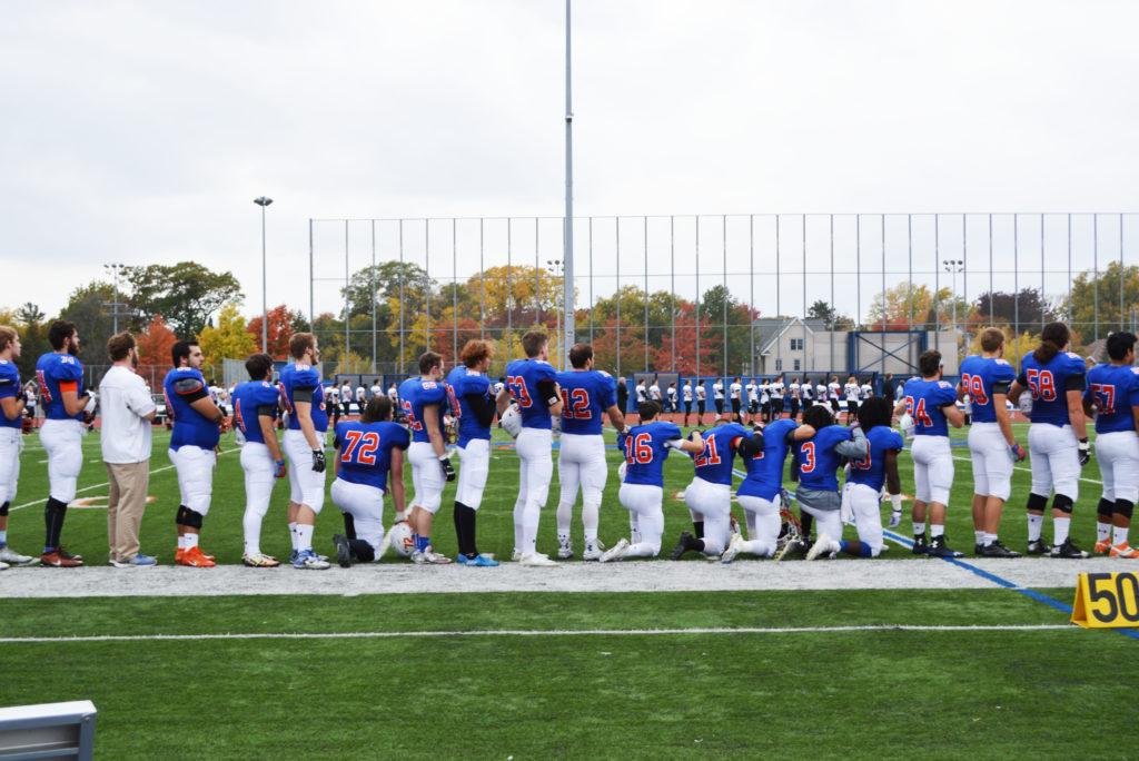 Members of the Macalester Football team kneel during the playing of the national anthem in solidarity with those facing racial discrimination. Photo by Rajnee Persaud '19.