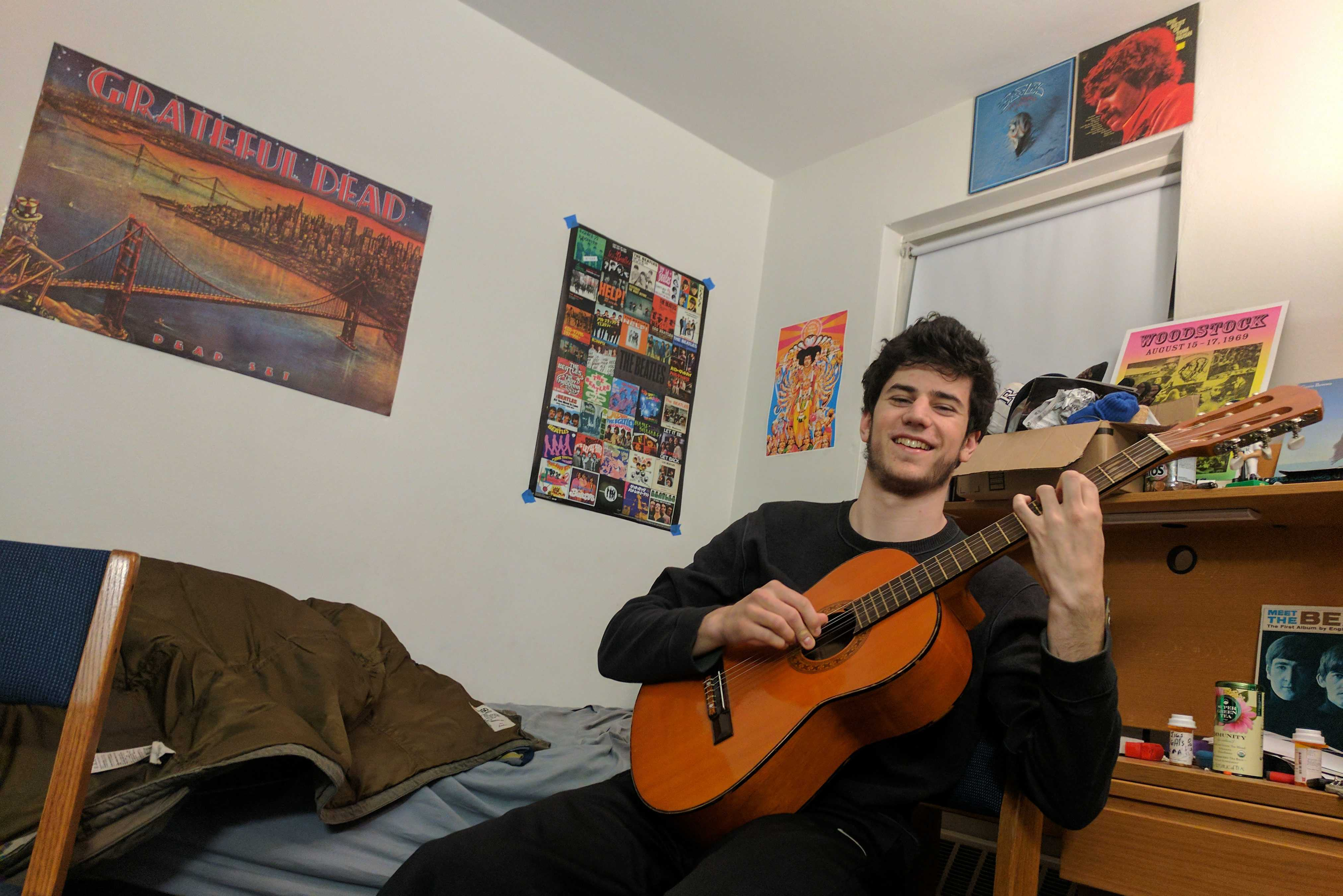 """Jacob Hill '19 of """"Vinyl Fridays"""" demonstrates his guitar skills in front of his classic rock posters. Photo by Nieberg '19."""