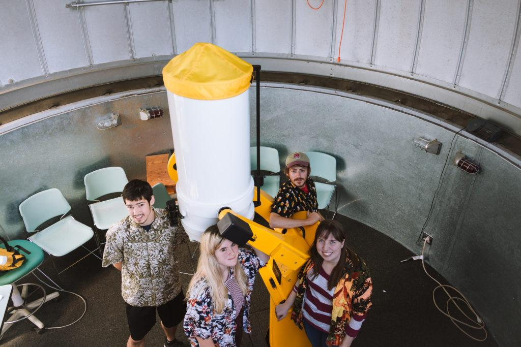 Macalester's Physics and Astronomy club seniors pose in front of the telescope in Macalester's observatory. From left to right, Brian Eisner '18, Catie Ball '18, Alex Gordon '18 and Liz Ruvolo '18.  Photo by Marin Stefani.