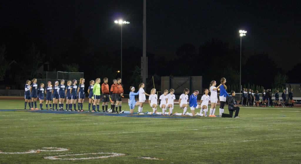 Members of the Macalester Women's Soccer team kneel in protest during the playing of the national anthem before their game  against Carleton College on Wednesday, Oct. 4. The Scots and Knights tied 1-1. Photo by Josh Koh '18.
