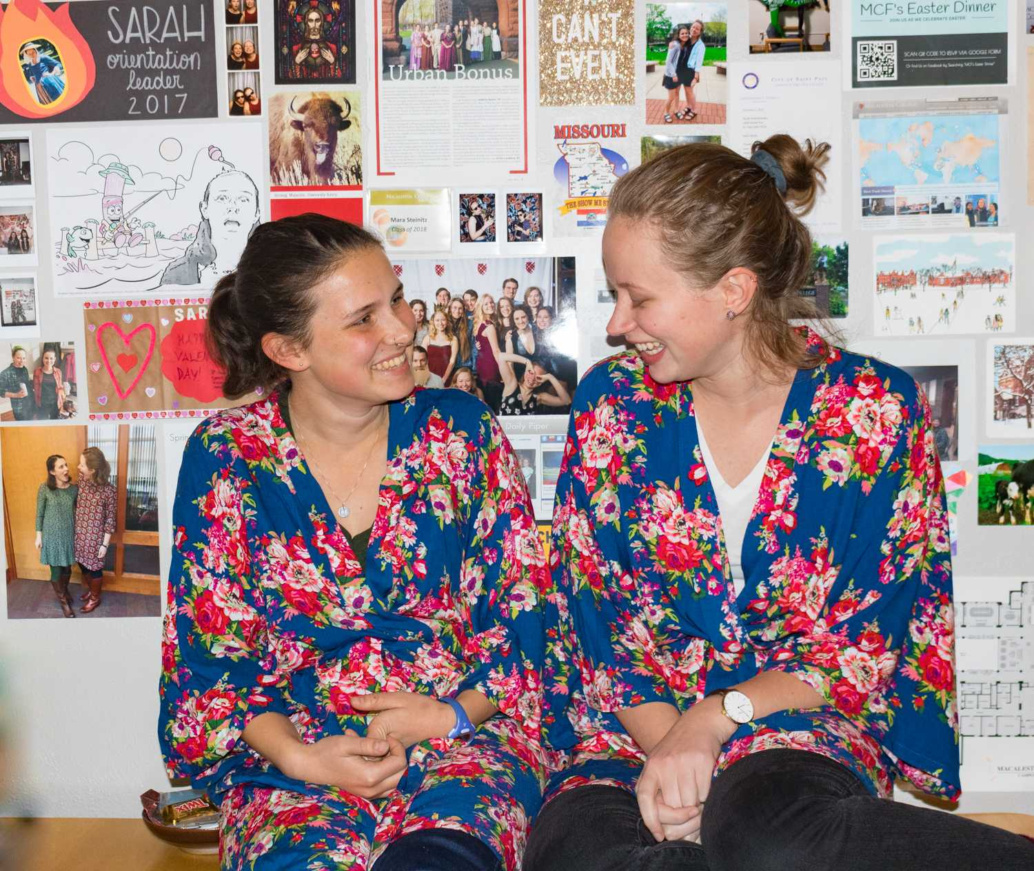 "Mara Steinitz '18 and Sarah Kolenbrander '18 sport matching bridesmaid robes in front of ""The Wall"" of memories in their living room. Photo by Lorna Sherwood Caballero '18."