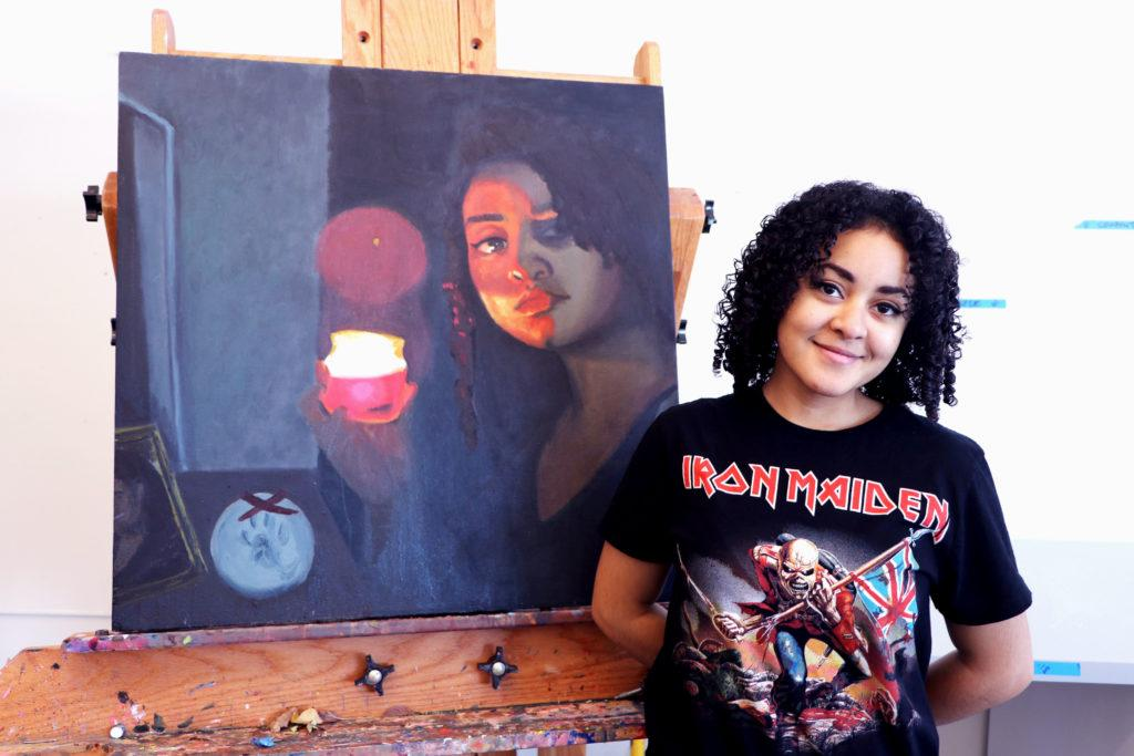 Aroura Bruins '18 poses next to her canvas self-portrait, inspired by Caravaggio. Photo by Celia Heudebourg '18