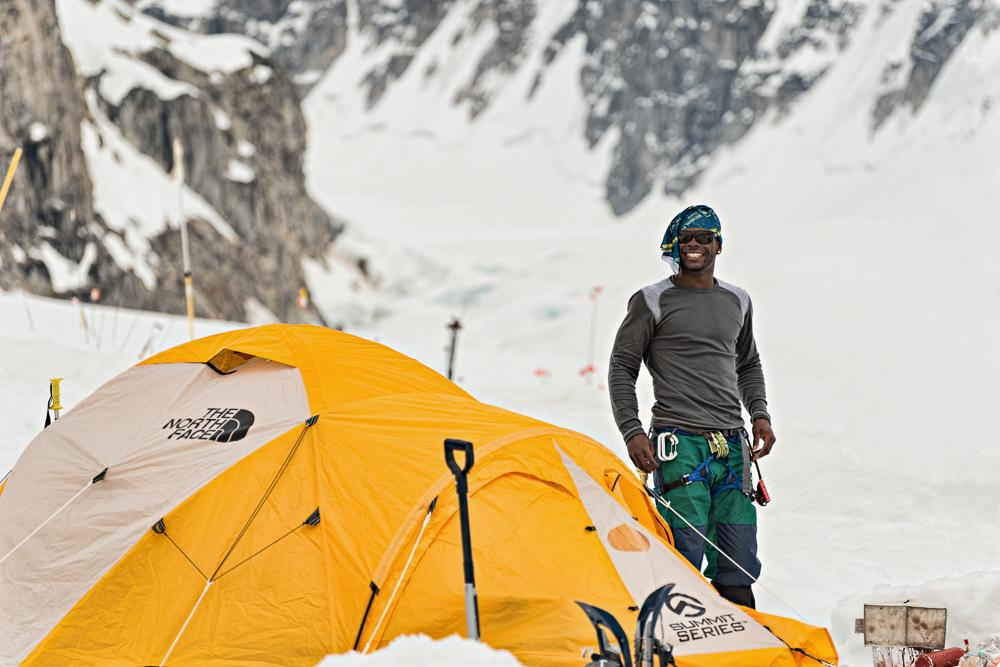 Climber Tyrhee Moore, smiling as he poses next to his tent at 14k. The second to last camp before the  summit, 14k welcomes mountaineers from all over the world. Photo courtesy of Hudson Henry.