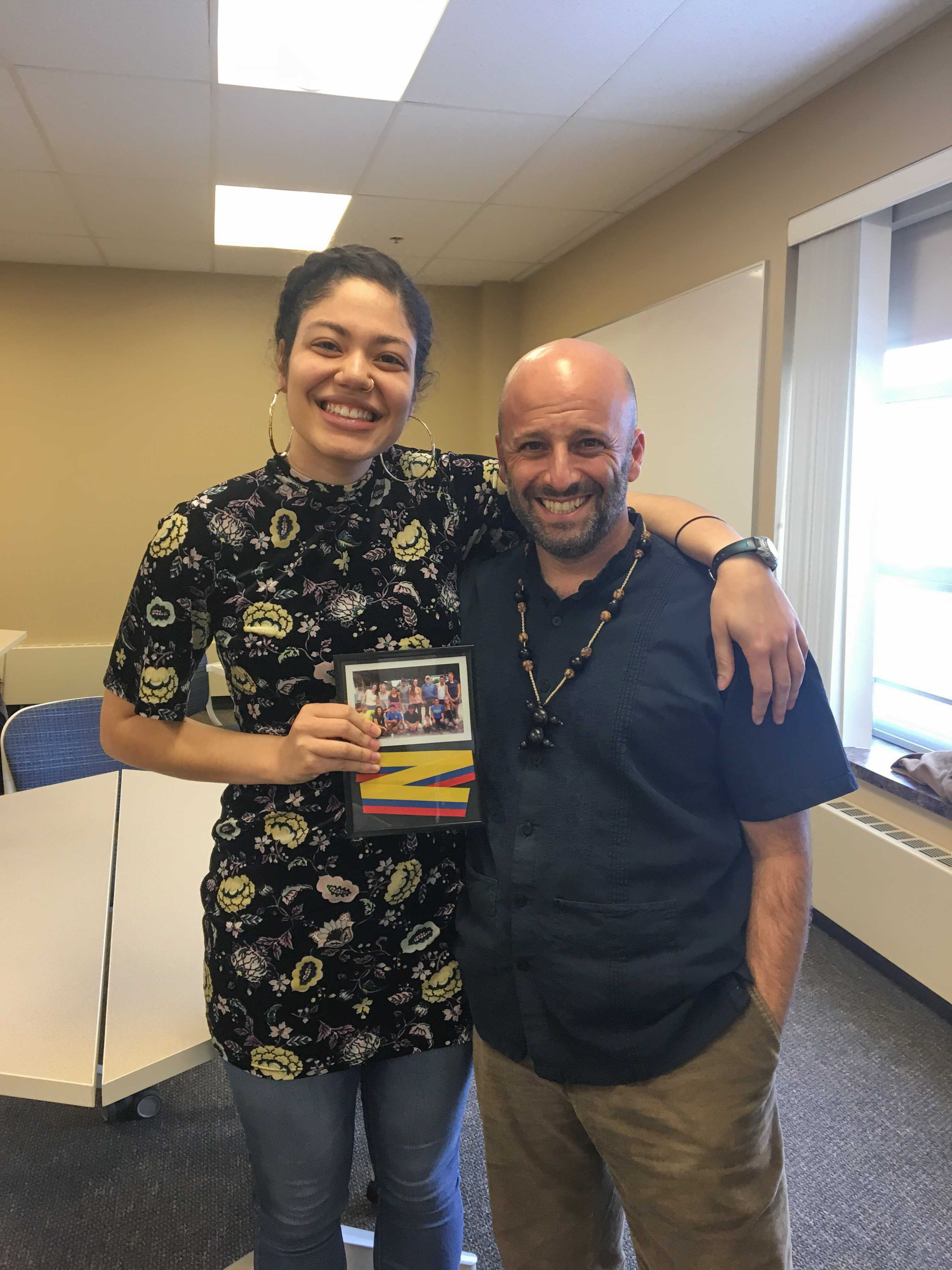 Giselle Lora '18 with Rehearsing Change program director, Daniel Bryan, with an award made of a section of the ribbon from the opening ceremony of the new stage in La Mariscal, Ecuador, a project Lora proposed while studying away.