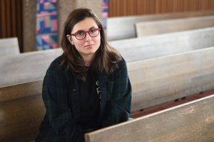 Liz Roten '18 sits in Weyerhaeuser Chapel.  Roten used Disability Services to get accommodations in her classes but said she still does much of the groundwork to make sure these accommodations happen. Photo by Maya Rait '18.
