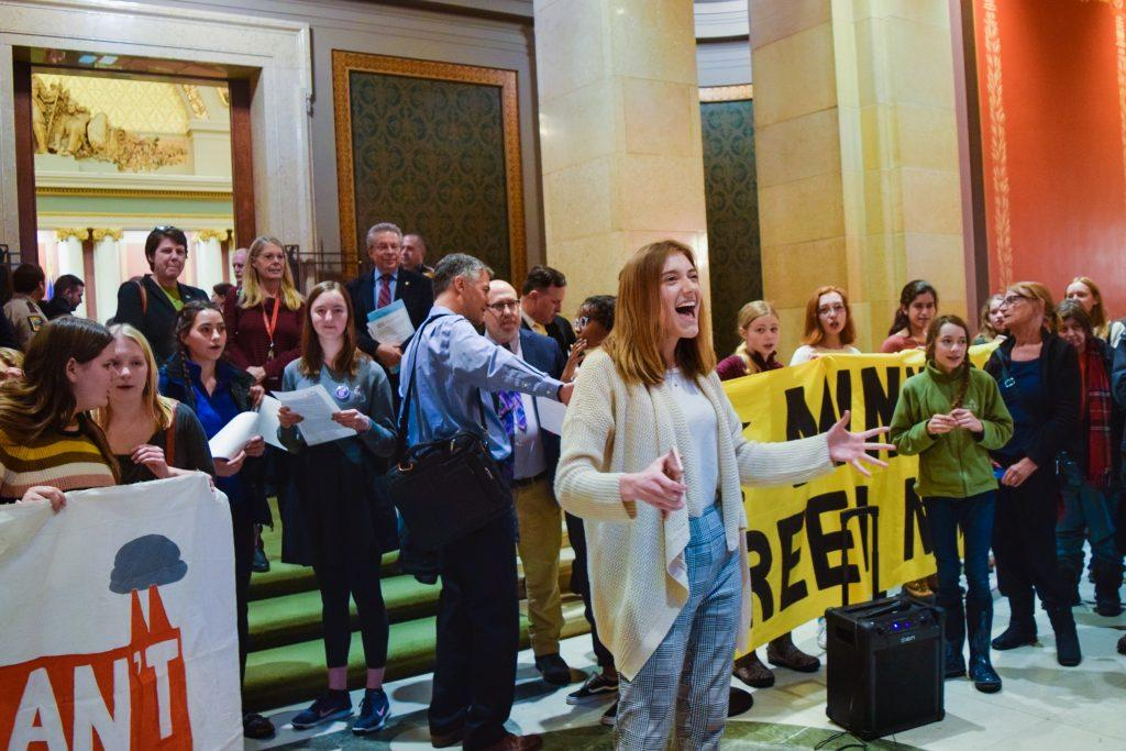 Maddy Fernands of Minnesota Can't Wait leads chant outside the Minnesota House Chamber. Photo by Linnea Henrikson '22.