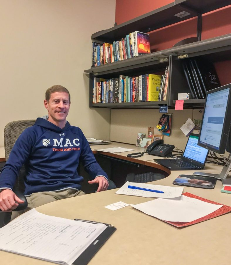 Coach Dan Schofer pictured in his office. He is the new Head Women's Cross Country Coach and Director of Track and Field. Photo by George Steinke '22.