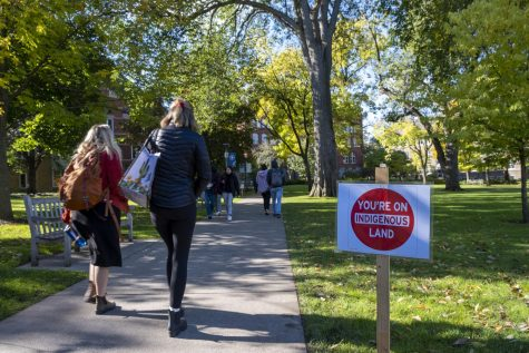 Students walk along Old Main lawn next to a sign from PIPE in honor of Indigenous Peoples