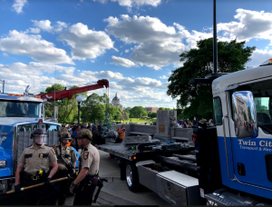 Workers from the Twin Cities Transport & Recovery company load the Christopher Columbus statue onto the back of a truck. Photo by Liam McMahon '20.