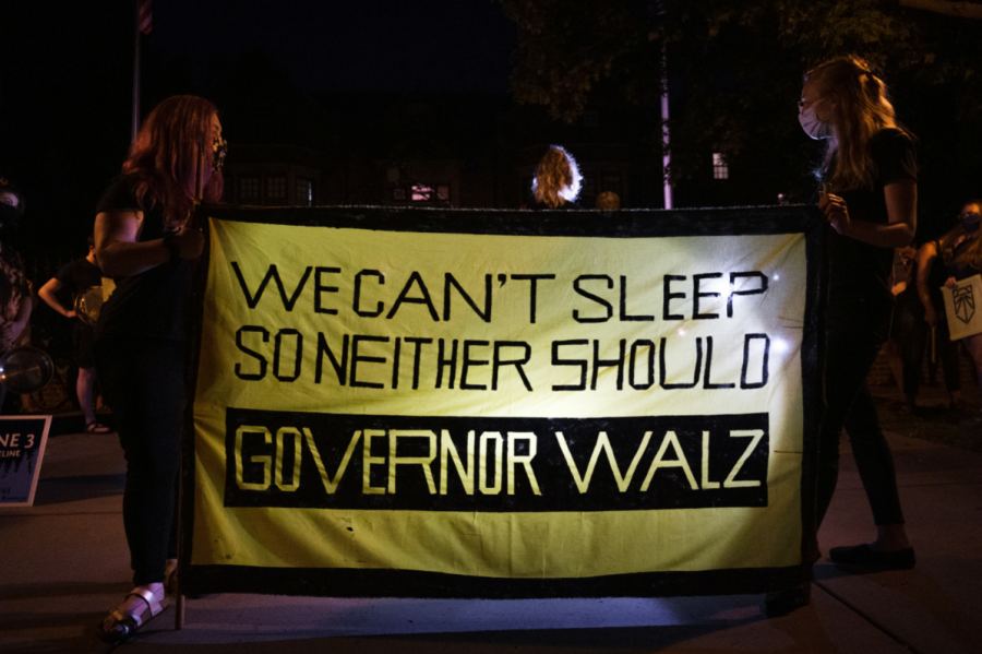 Protesters with Sunrise Movement Twin Cities hold a banner outside the governor's mansion during the Wake Up Walz protest on Thursday night. Photo by Kori Suzuki '21.