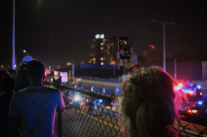 A bystander livestreams from the street overlooking I-94 as Minnesota State police surround and arrest more than 600 people calling for all votes to be counted in the presidential election on the highway below on November 4, 2020. Photo by Kori Suzuki '21.