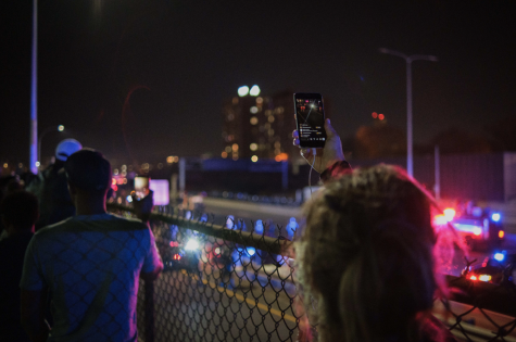 A bystander livestreams from the street overlooking I-94 as Minnesota State police surround and arrest more than 600 people calling for all votes to be counted in the presidential election on the highway below on November 4, 2020. Photo by Kori Suzuki