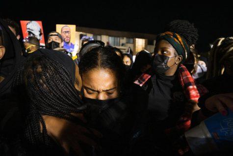 Individuals embrace in Brooklyn Center Friday night. Photo by Kori Suzuki '21